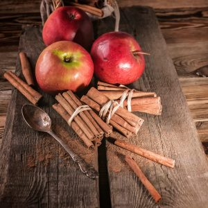 Cinnamon sticks and ripe apples on a wooden background. Low key lighting